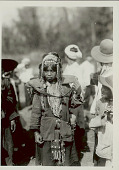 view Woman in Costume with Shell, Bead, and Feather Headdress, And Ornaments, Carrying Burden Basket with Yoke; Group Nearby 1931 digital asset number 1