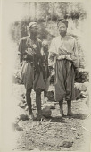 view Three Men in Costume, One Wearing Charm Box, Near Masonry Wall n.d digital asset number 1