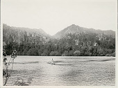 view Man in Canoe on River; Mountains in Background digital asset: Man in Canoe on River; Mountains in Background