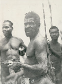 view New Guinea Man Wearing Breechcloth, Two Other Men in Background, with Spear 1891 digital asset number 1