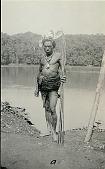 view New Guinea Man Wearing Rattan Fiber Breech-Cloth, Ornaments, Feather Headdress and Holding Spears Near Water 1891 digital asset number 1