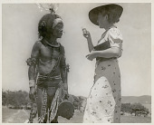 view Non-Native Woman Admonishes Man (Her Cook) in Ceremonial Dance Costume Who Is Wearing Ornaments and Holding Drum digital asset: Non-Native Woman Admonishes Man (Her Cook) in Ceremonial Dance Costume Who Is Wearing Ornaments and Holding Drum