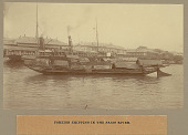 view Passenger Steamship and Cascos (Flat-Bottomed Boats) on River; Large Commercial Buildings in Background digital asset: Passenger Steamship and Cascos (Flat-Bottomed Boats) on River; Large Commercial Buildings in Background