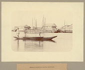 view Young Man in Costume in Banca (Round-Bottomed Boat) with Woven Mat Cover and Outrigger on River; Two Story Wood Frame Buildings in Background digital asset: Young Man in Costume in Banca (Round-Bottomed Boat) with Woven Mat Cover and Outrigger on River; Two Story Wood Frame Buildings in Background