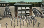 view Group of Men, Prisoners, in Uniform, Some with Musical Instruments Inside Prison Yard Near Masonry Wall and Buildings digital asset: Group of Men, Prisoners, in Uniform, Some with Musical Instruments Inside Prison Yard Near Masonry Wall and Buildings