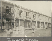 view Group in Costume, Some with Head Baskets, in City Street Outside Two-Story Masonry, Brick and Wood Commercial n.d digital asset number 1