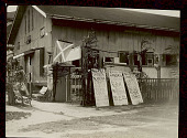 view View of Cinematograph (Motion Picture Theatre) Showing Ticket Office, Marquee, Posters, and Benches Outside Tin Building 05 SEP 1925 digital asset number 1