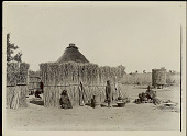 view Woman and Children Outside Brush Fence Surrounding Thatch House; Mealie Cache, Mortar and Pestle, Pots, and Basket Nearby n.d digital asset number 1