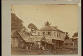 view View of Town Showing Group in Costume Outside Wood Frame House and Plank Houses with Thatch Roofs; Gas Lantern Nearby n.d digital asset number 1