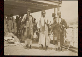 view Three Men, Vendors from Interior of Sierra Leone, in Costume And Selling Spears and Other Goods to Crew on Boat Deck; Group Of Men, Vendors from Syria, in Costume and Selling Clothes Behind Them n.d digital asset number 1