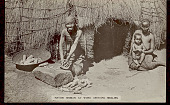 view Aged Bantu Woman Grinding Mealies with Stone on Groundstone; Corn In Basket and Woman with Child Nearby; Both in Costume Outside Pole and Thatch House n.d digital asset number 1