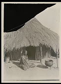 view Woman in Costume Outside Thatch House; Metal Kettle And Containers Nearby n.d digital asset number 1