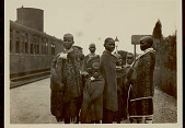 view Group of Women and Children in Costume and Wearing Blankets On Roadway at Station; Train Nearby 11 MAR 1922 digital asset number 1