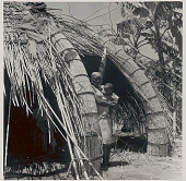 view Woman in Costume, Nursing Infant in Doorway of Mushonge (Portion of House) Undergoing Repair and Showing Method of Construction with Bamboo Pole; Another Woman Inside 1953 digital asset number 1