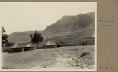 view View of Mount Insizwa, Southwest Side, and Village of Round Mud Houses with Thatch Roofs; Woman Nearby 24 MAR 1922 digital asset number 1