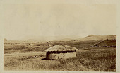 view View of Round Mud House with Thatch Roof; Village and Mountains in Background n.d digital asset number 1