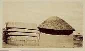 view Round Mud House with Thatch Roof and Thatch Fence; Woman In Costume Nearby; Other Houses, Animal, and Woman in Background n.d digital asset number 1