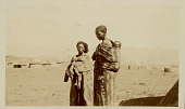 view Two Women Wearing Blankets, One Carrying Child on Back; Village and Mountains in Background n.d digital asset number 1