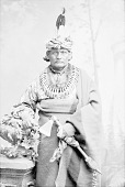 view Standing Bear in Partial Native Dress with Bear Claw Necklace and Headdress and Holding Tomahawk n.d digital asset number 1