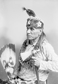 view Iowa Man Neu-monya or Walking Cloud in Partial Native Dress with Headdress and Bear Claw Necklace and Holding Fan and Pipe-tomahawk n.d digital asset number 1