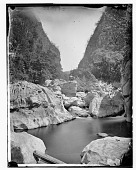 view Man standing on boulder in Ravine by river in San Mateo digital asset: Man standing on boulder in Ravine by river in San Mateo