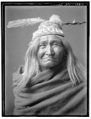view Edward S. Curtis papers and photographs digital asset: Portrait of Apache man wearing feathered cap. Published as The Apache