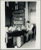 view Henry B. Collins studying human skulls in a work area at the SI Department of Anthropology 1928 digital asset number 1