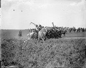view Large group of riders on horseback, some carrying feathered staffs and American flags digital asset: Large group of riders on horseback, some carrying feathered staffs and American flags