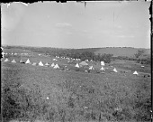 view Broad view of powwow camp ground showing tipis and tents digital asset: Broad view of powwow camp ground showing tipis and tents