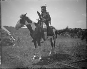 view Man wearing regalia on horseback digital asset: Man wearing regalia on horseback