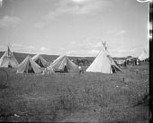 view Cluster of tipis and tents in powwow camp ground digital asset: Cluster of tipis and tents in powwow camp ground