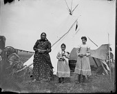 view Woman and two girls standing in front of tipi on powwow camp ground. One girl is holding a puppy digital asset: Woman and two girls standing in front of tipi on powwow camp ground. One girl is holding a puppy