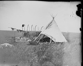 view Individual camp on powwow camp ground showing tipi, wagon, meat draped over pole to dry, and several people sitting by fire in front of tipi digital asset: Individual camp on powwow camp ground showing tipi, wagon, meat draped over pole to dry, and several people sitting by fire in front of tipi