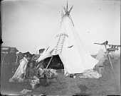 view Individual camp on powwow camp ground showing tipi, meat draped over pole to dry, wagons, cooking paraphernalia, and several people sitting in front of tipi digital asset: Individual camp on powwow camp ground showing tipi, meat draped over pole to dry, wagons, cooking paraphernalia, and several people sitting in front of tipi