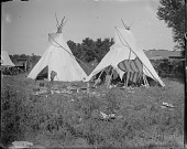 view Two tipis on powwow camp ground with remains of fire in front and wagons in background digital asset: Two tipis on powwow camp ground with remains of fire in front and wagons in background