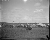 view General view of powwow showing people, tents, tipis, and horses digital asset: General view of powwow showing people, tents, tipis, and horses