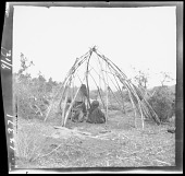 view Jicarilla Apache frame construction for brush hut; three Indians seated within. 1903 digital asset number 1
