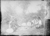 view Four Men Seated at Moccasin Game Guessing the Location of the Marked Bullet, All in Partial Native Dress with Headdresses, Two with Drums 1910 digital asset number 1