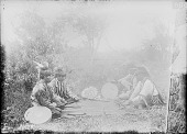 view Four Men Seated at Moccasin Game, Hiding the Bullets, All in Partial Native Dress Wtih Headdresses, Two with Drums, All with Arrows 1910 digital asset number 1