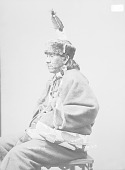 view Portrait (Profile) of Na-Wat-E-Na (Picking Up Something) in Partial Native Dress with Headdress and Ornaments and Holding Pipe 1896 digital asset number 1