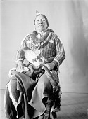 view Portrait (Front) of Ray-Tah-Cotz-Tay-Sah (Roaming Chief) in Partial Native Dress with Peace Medal, Bear Claw Necklace and Holding Fan FEB 1902 digital asset number 1