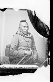 view Portrait (Front) of As-Sau-Taw-Ka (White Horse) in Partial Native Dress with Civil War Jacket and Ornaments and Holding Pistol and Pipe-tomahawk 1868 digital asset number 1