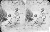 view Two Girls and Boy Looking at Rabbit Skin, All in Native Dress, One with Headdress; Bow and Arrows Nearby 1873 digital asset number 1