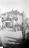 view Ceremony, Tasap Kachina Costume with Body Paint Dancing in Plaza; Spectators on Adobe House Cluster Behind Them n.d digital asset number 1