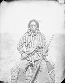 view War Captain with Chief Hunter in Partial Native Dress with Ornaments and Bear Claw Necklace and Holding Rifle, Spear, Gunpowder Horn and Bag 1884 digital asset number 1