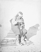 view Governor of Village in Native Dress with Ornaments, Seated On Blanket Using Wooden Drill 1880 digital asset number 1