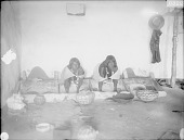view Two Women Grinding Wheat On Metates Inside Adobe House, Both in Native Dress with Squash Blossom Necklaces, Clay Pots and Basket Nearby 1899 digital asset number 1