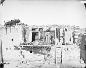 view Tota, Hopi Married To Zuni Woman, On Adobe House with Wife and Three Children; Blankets Hanging On Wall Behind Group 1879 digital asset number 1