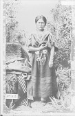 view Portrait (Front) of Woman in Native Dress with Concha Belt and Ornaments, Buffalo Robes? and Blanket Nearby 1880 digital asset number 1