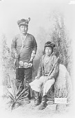 view Portrait of Charlie? and Atta-Kai-Bi-Tzu-Ih, Both in Partial Native Dress with Ornaments, One with Concha Belt; Both Holding Rifles, One with Pistol 1880 digital asset number 1